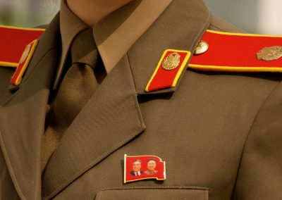 An-English-speaking-guide-at-the-Victorious-Fatherland-Liberation-War-Museum-in-Pyongyang-wore-a-badge-depicting-North-Korea's-leaders